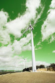 Wind energy turbines over green cloudy sky. Green energy concept — Stock Photo
