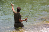 Fisherman, taking the line, while standing inside the river flow — Stock Photo