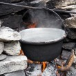 Old pot on fire outside — Stock Photo