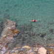 Woman and child swimming in blue sea seen from above — Stock Video