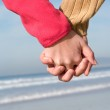 Lovers couple holding hands on beach at winter — Стоковое фото