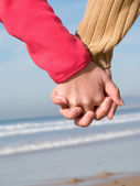 Lovers couple holding hands on beach at winter — Stock Photo