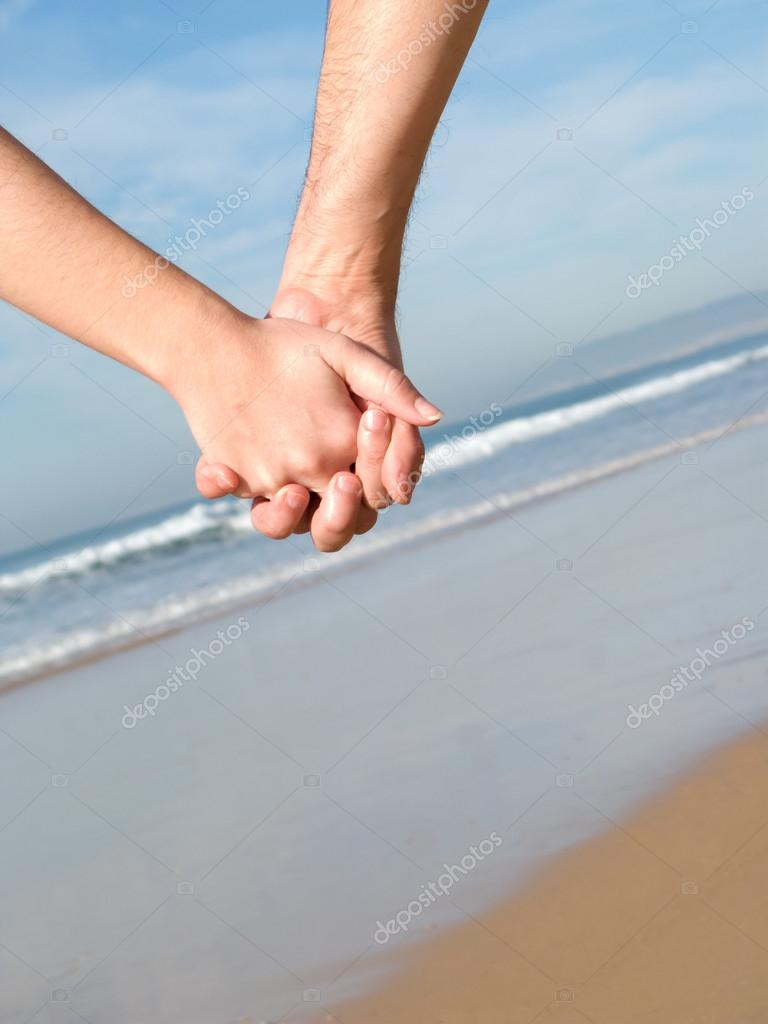 Lovers couple holding hands on beach at winter — Stock Photo #13297250