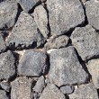 Basalt (volcanic rock) wall made with irregular blocks. — ストック写真