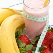Smoothie made with strawberries and bananas and a measure tape - Stock Photo