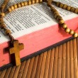 Open Bible with rosaries-beads crucifix on a straw table — Stock Photo #13318732