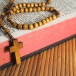 Open Bible with rosaries-beads crucifix on a straw table — Stock Photo #13318734