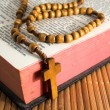Open Bible with rosaries-beads crucifix on a straw table — Stock Photo