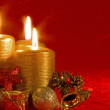 Three burning candles in a Christmas setting with seasonal decorations — Stock Photo