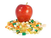 Red apple vs. food supplements in pills — Stock Photo
