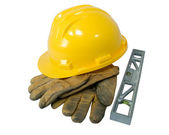 Yellow hardhat, old leather gloves and a level isolated on white background — Stock Photo