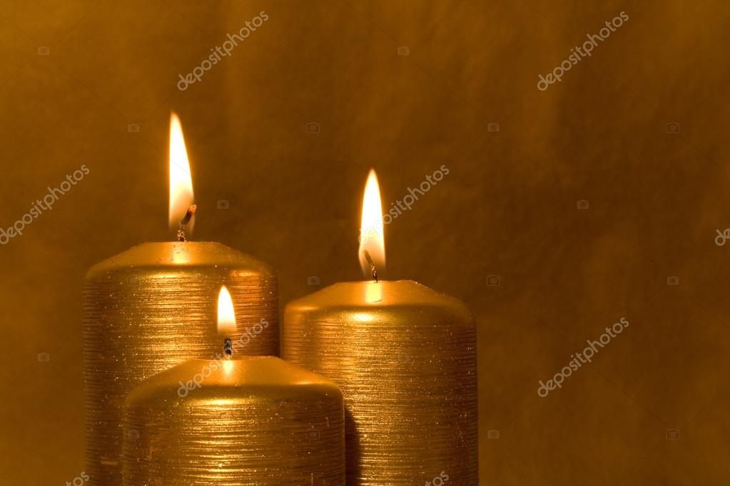 Three golden candles burning in the grunge background — Stock Photo #13319079
