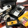Old, vintage film cameras with photo paper, negative roll and case — Stock Photo #13320405