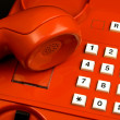 Stock Photo: Old red telephone close-up detail