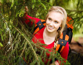 Young woman hiker hiding under a tree — Stock Photo