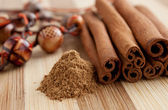 Cinnamon sticks with ground cinnamon and beads — Stock Photo
