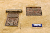 Coat of arms, fragment of brick wall and street nameplate in War — Stock Photo