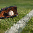 Baseball mitt and ball in grass by field stripe — Stock Photo