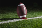 College football on a tee at night ready for kick off — Stock Photo