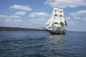 Tall ship with American flag sailing on blue waters — Stok fotoğraf