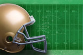 Gold football helmet in profile view against a field with diagra — Stock Photo
