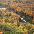 Small river and Lake of the Clouds in full autumn color - Stock Photo