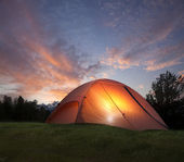 Tent with light inside at dusk near the Grand Teton mountains — Stockfoto