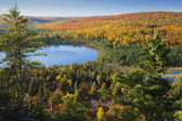 Small blue lake amid hills in autumn color — Stock Photo