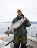 Happy fisherman in holds big silver salmon — Stock Photo