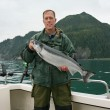 Stock Photo: Happy fishermin holds big silver salmon
