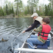 Young boy fisherman catches a walleye — Stock Photo #26337687