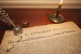 Declaration of Independence with glasses, quill pen and candle — Stock Photo