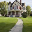 Victorian house with lawn and sidewalk on sunny afternoon — Stock Photo #26676687