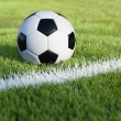 Soccer ball sits on grass field with white stripe — 图库照片