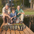 Two men and a boy posing with catch of fish — Stock Photo