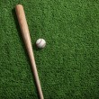 Baseball and bat on green turf viewed from above — Stock Photo