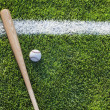 Baseball bat and ball on grass field viewed from above — Stock Photo