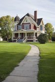 Victorian house with lawn and sidewalk on sunny afternoon — Stock Photo