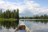 Canoe with fishing gear heading out on northern lake — Stock Photo