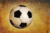 Traditional soccer ball on grunge textured background — Stock Photo