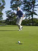 Golfer celebrates sinking putt on green — Stock Photo