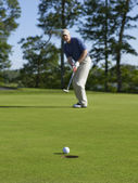 Golfer sinks putt on green — Stock Photo