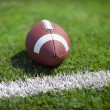 College football at yard line or goal with defocused background — Stock Photo