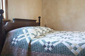 Old fashioned bed with quilt and oil lamp — Stock Photo
