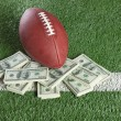 NFL football on field with a pile of money — Stock Photo