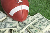 College style football on field with a pile of money — Stock Photo