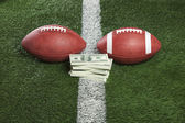 Pro and college style footballs with money between — Foto Stock
