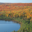 Colorful fall trees on hills by lake in northern Minnesota — Stock Photo #33823371