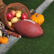 Football with a cornucopia on a grass field — Stock Photo