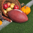 Football with a cornucopia on grass field — Stock Photo